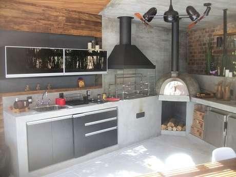 57. Espaço gourmet de uma casa conta com a presença de uma churrasqueira de vidro e forno a lenha. Fonte: Pinterest