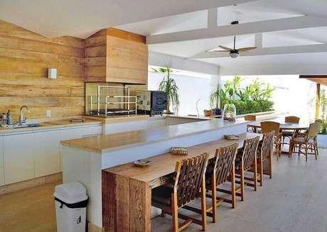 39. Espaço gourmet para reunir família e amigos com bancada de madeira extensa. Fonte: Casa e Festa