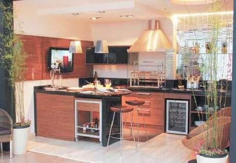 47. Área de lazer pequena com pendentes metálicos, banquetas, adega embutida e churrasqueira de vidro. Fonte: Zap Móveis