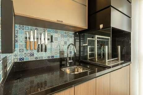 4. Parede de ladrilho hidráulico azul, bancada preta e churrasqueira com lateral de vidro. Projeto por LAM Arquitetura & Interiores