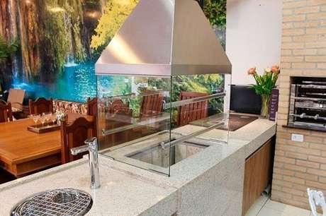 3. Terraço gourmet com churrasqueira de vidro instalada sobre uma bancada de granito. Fonte: Pinterest