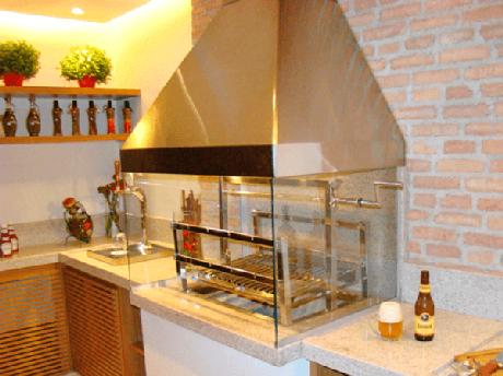 28. Varanda gourmet com armários de madeira, bancada de granito e churrasqueira de vidro. Fonte: Pinterest