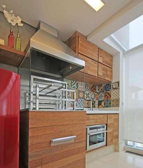 33. Varanda gourmet com ladrilho na pia e churrasqueira com lateral de vidro e coifa de inox. Projeto por Officina 44
