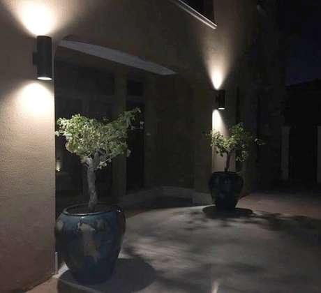 11. Aqui, as arandelas externas iluminam os lados da porta. Projeto de Espaço Pau Brasil Arquitetura