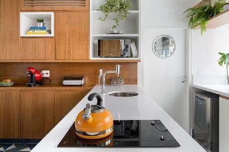 19. Bancada de cozinha feita em silestone branco com armário de madeira e cooktop – Foto: Tria Arquitetura