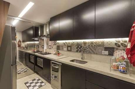 21. Cozinha moderna com armários planejados preto com iluminação em armário aéreo e bancada de cozinha com pia e cooktop – Foto: Conseil Brasil