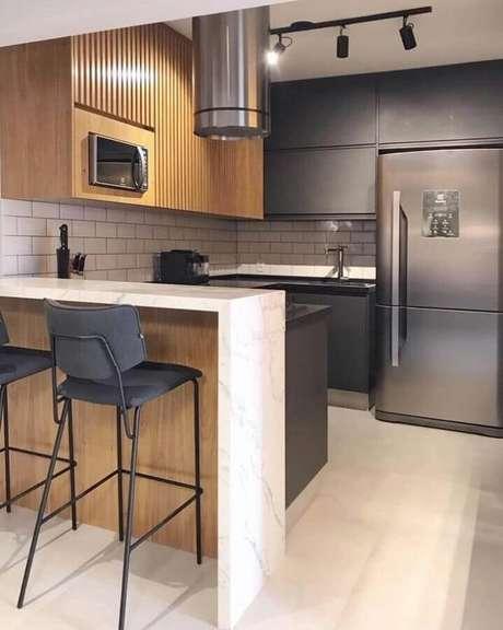 25. Bancada de mármore para cozinha pequena com armário planejado preto e em madeira – Foto: Duda Senna