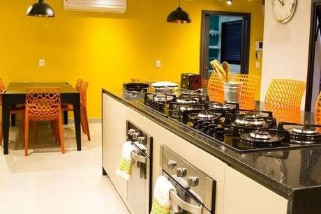 29. Bancada para cozinha com cooktop e paredes amarelas – Foto: Abreu Coimbra Arquitetura