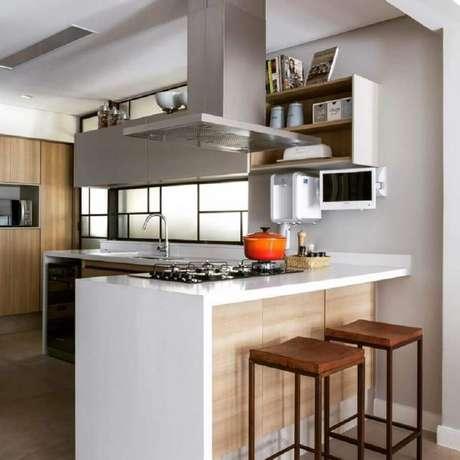 32. Bancada de cozinha feita em nanoglass com cooktop e coifa de inox – Foto: Ana Yoshida Interiores