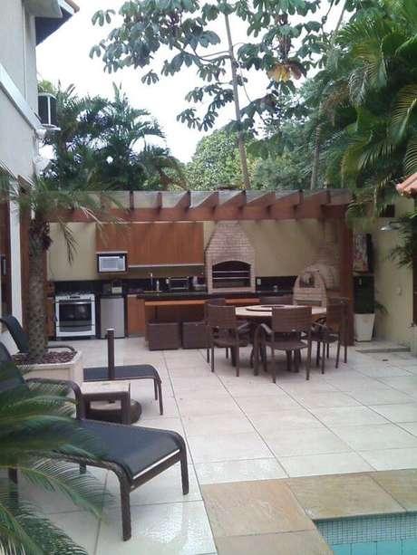 10. A churrasqueira de tijolo chama a atenção para a área externa. Projeto de Margareth Salles