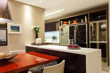 38. Cozinha americana decorada com armários planejados e mesa vermelha acoplada na bancada para cozinha – Foto: Decor Salteado