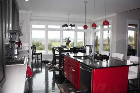 69. Cozinha com bancada de granito e armários em tons de vermelho. Fonte: Total Construção