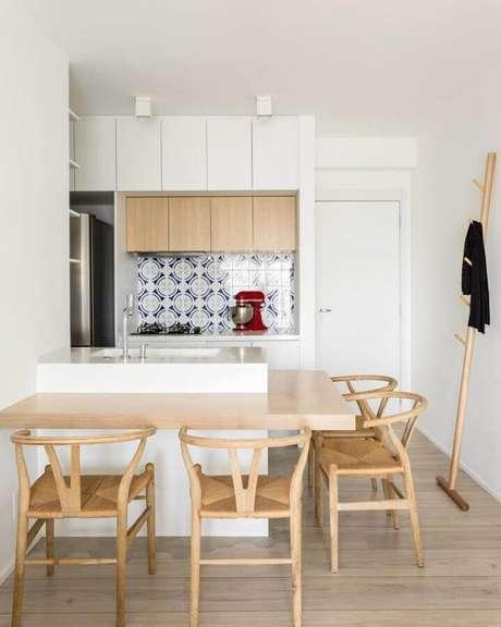46. A bancada de cozinha feita em madeira levou um toque aconchegante para a cozinha toda branca – Foto: Gabriel de Lucca
