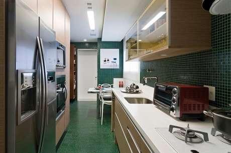 51. Decoração com pastilhas verdes e bancada para cozinha feita em corian – Foto: Diego Revollo