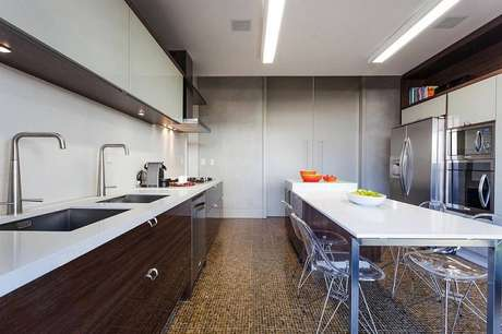 10. O gabinete de cozinha pode ser feito em tons mais escuros, com armários claros para contrastar. Projeto por Marchetti Bonetti.