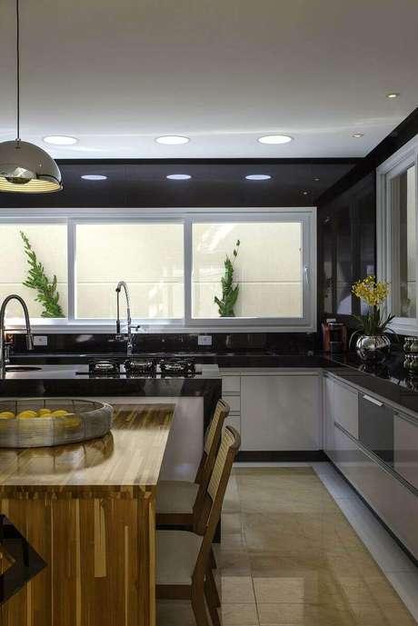 49. O gabinete de cozinha com porta envernizadas também remete ao luxo. Projeto de Iara Kilaris