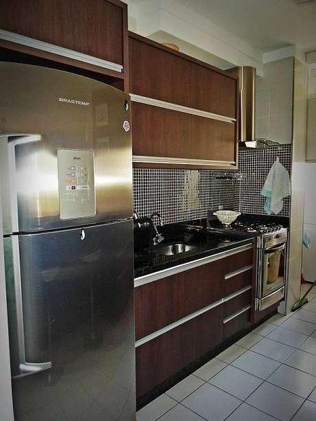 19. O gabinete de cozinha com móveis escuros deixa o espaço fechado, mas muito elegante. Projeto por Alan Tozo.