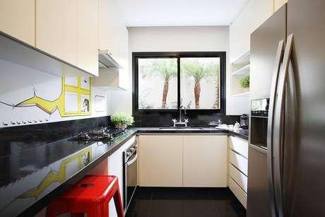 27. Escolher um gabinete de cozinha com portas largas é ideal para guardar panelas. Projeto por Mès Arquitetura.