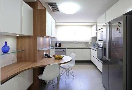 34. Para quem não quer chamar atenção para a área do gabinete de cozinha, investir em outros móveis de destaque pode ser a solução. Projeto por Fernanda Renner.