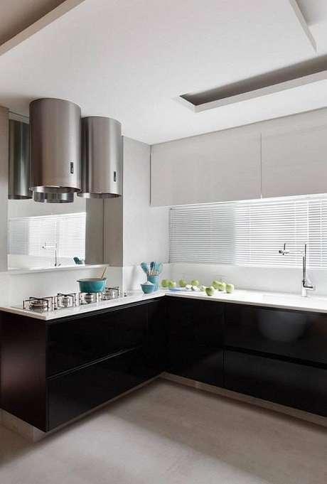 36. O gabinete de cozinha preto com armários brancos deixa a cozinha moderna e ainda ampla. Projeto por Guilherme Torres.