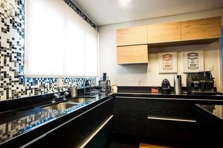 37. O gabinete de cozinha preto ganha graça com a parede de pastilhas. Projeto por 2 Arquitetos.