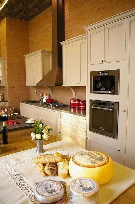 39. O gabinete de cozinha pode ter frisos ou rebaixos e dar o tom do estilo do ambiente. Projeto por Adriana Giacometti.