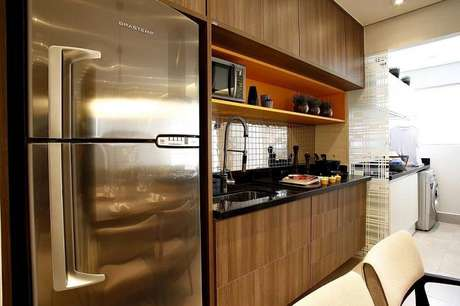 40. A sobriedade do gabinetede cozinha é quebrada com a prateleira colorida. Projeto por By Arquitetura.