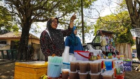 Siti Ain (à dir.) com sua mãe, que vende comida e bebida do lado de fora da escola