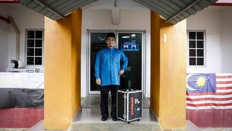 """Mahyuddin Ismail posa com seu kit """"anti-histeria"""" do lado de fora de sua clínica na Universidade de Pahang"""