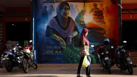 Mulher caminha em frente a mural no mercado central de Siti Khadijah em Kota Bharu
