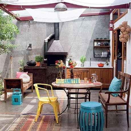 24. Área externa decorada com móveis de madeira e garden seat azul – Foto: Nô às Nove