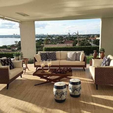 30. Decoração para varanda ampla com dupla de garden seat estampado e móveis de vime – Foto: Cassio Veiga Casa