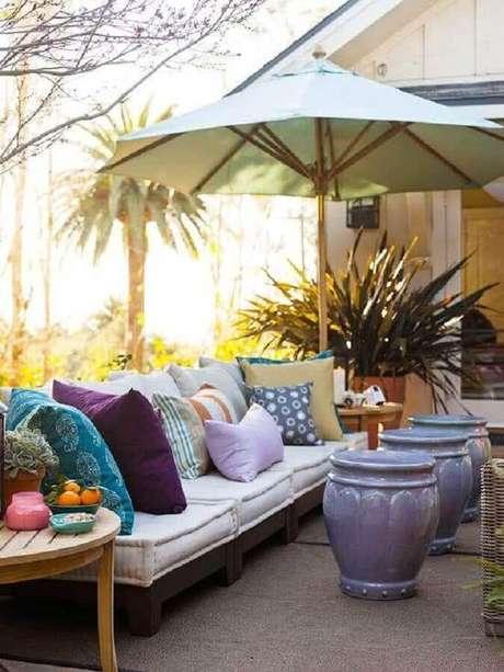 33. Varanda decorada com almofadas coloridas e trio de garden seat lilás – Foto: Revista Micasa