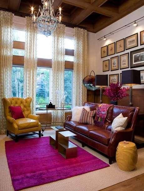 49. Sala de estar decorada com sofá de couro, vários quadros,. tapete rosa e garden seat amarelo – Foto: Home Apartment