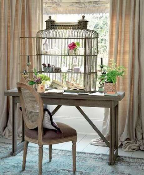 15. Gaiola decorativa serve de prateleira para escrivaninha de madeira. Fonte: Decoração e Ideias