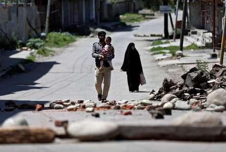 Família da Cashemira passa por bloqueio feito por moradores locais para impedir que forças de segurança da Índia entrem na região. Srinagar, 20/8/2019. REUTERS/Adnan Abidi