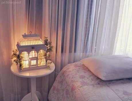 70. Gaiola decorativa serve de luminária de mesa na decoração do quarto. Fonte: Decoração e Arte