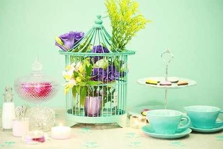 7. Gaiola decorativa com flores enfeita o centra de mesa da casa. Fonte: Pinterest