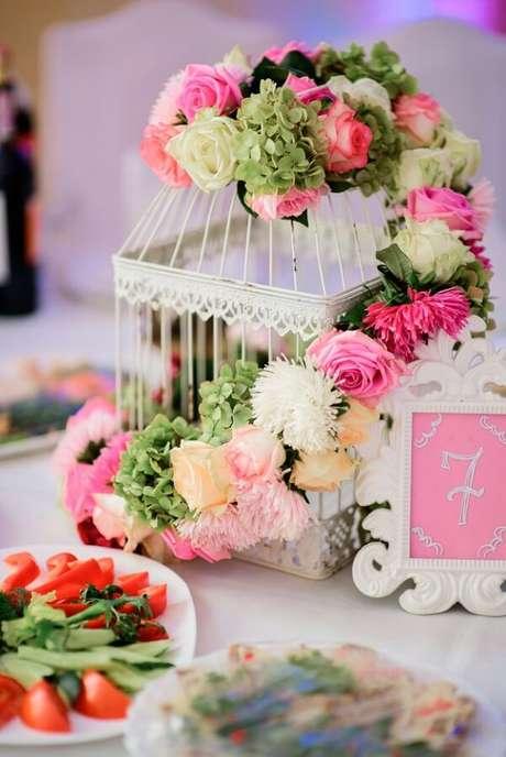 51. Gaiolas decorativas com flores naturais enfeitam o centro de mesa. Fonte: Pinterest