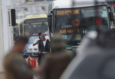 Refém encobre o sequestrador ao descer do ônibus na ponte Rio-Niterói.