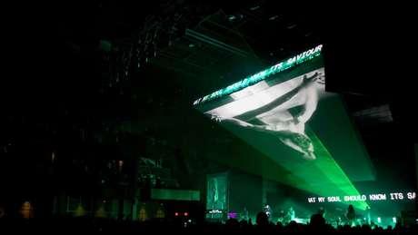 Uma imagem criada por computador de Jesus Cristo na cruz ilumina o palco da banda Hillsong United, a face mais visível e bem sucedida da igreja Hillsong
