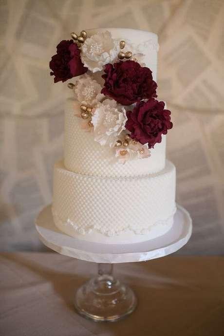 25. Bolo de casamento branco com flores na cor marsala – Por: Pinterest