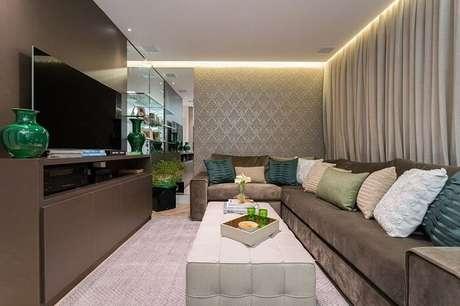 30. Tecido para sofá de veludo e diversas almofadas complementam a decoração do ambiente. Projeto por Helena Koki