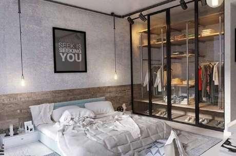 26. Quadros para decoração de quarto moderno com parede de cimento queimado e closet com porta de vidro – Foto: Wood Save