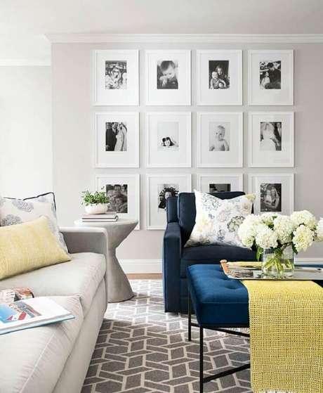 31. Quadros decorativos com moldura branca para sala com poltrona azul – Foto: Elle Decor