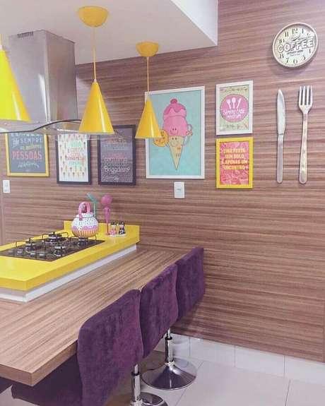 36. Decoração colorida com quadros decorativos para cozinha com revestimento de madeira e pendentes amarelos – Foto: Decoração de Casa
