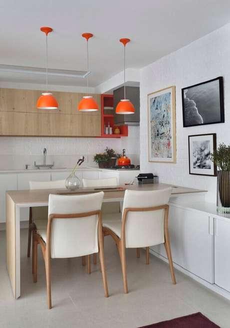 7. Decoração clean com quadros decorativos para cozinha planejada em tons neutros com luminária pendente laranja – Foto: Vai com Tudo