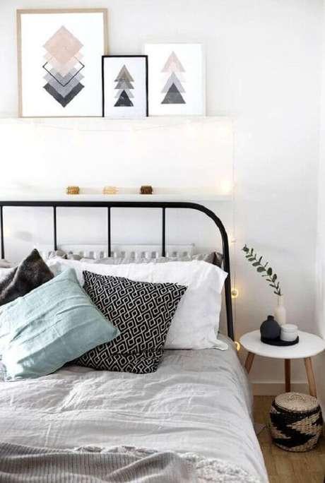 54. Decoração com quadros apoiados em prateleira estreita para quarto com cama de ferro preto – Foto: House Design