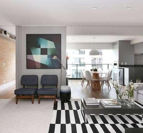64. Quadros para decoração de sala ampla e moderna com tapete listrado preto e branco – Foto: Ideias Decor