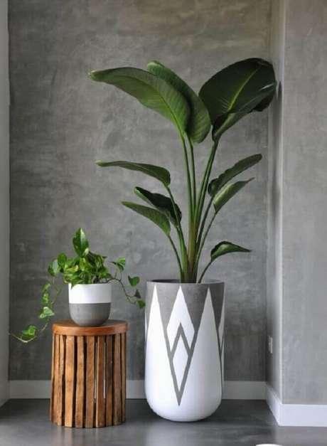 72. Vasos decorativos de tamanhos diferentes combinando com a parede de cimento queimado – Foto: Interiors Addict